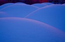 Snökullar fotograferade i blå timmen